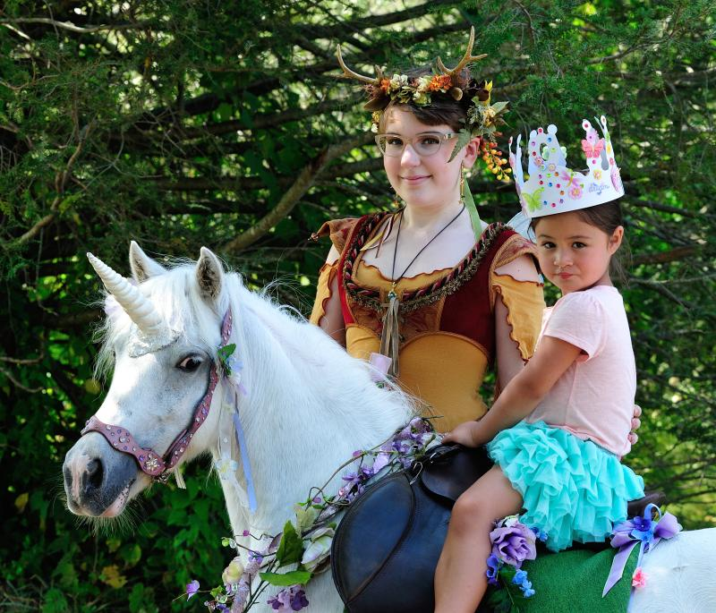 birthday girl riding a unicorn at her fairy unicorn party at Schooley Mill Park